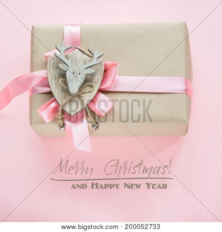 Christmas gift box for girl with pink ribbon and reindeer on pink. Square image.