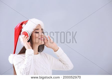 Beautiful young woman in Santa hat listening to Christmas music on light background
