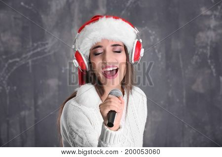 Beautiful young woman in Santa hat singing Christmas songs on grunge background