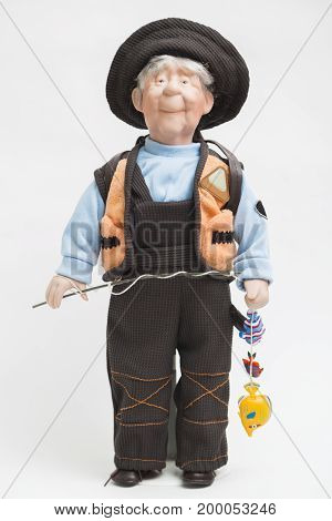 Ceramic doll of an old elderly positive smiling fisherman with fishing pole with colorful exotic fishes in his hands in brown overall, blue pullover, orange vest and textile hat on white background.