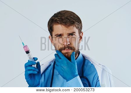 Man with a beard on a light background holds a syringe, medicine, medical gown, portrait, doctor.