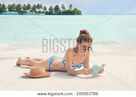 Beautiful young woman reading book while lying on sea beach