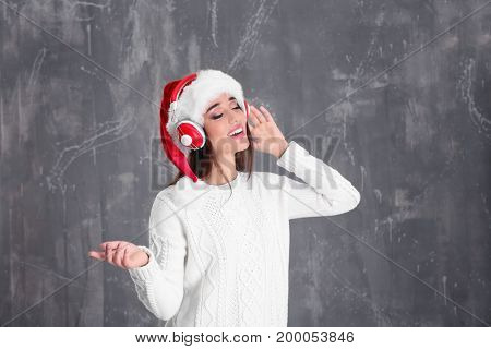 Beautiful young woman in Santa hat listening to Christmas music on grunge background