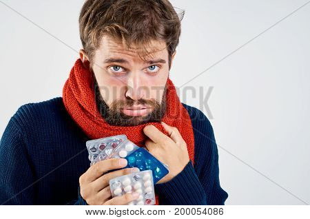 Man with a beard on a light background holds a tablet, portrait, emotions, flu, illness, sick person in a scarf.