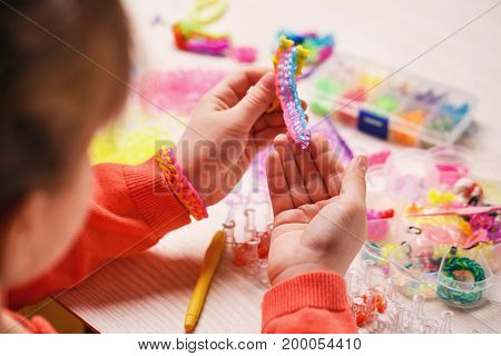extracurricular activities, group, education and handwork concept - colored rubber bands for weaving accessories in the hands of a girl on a wooden background