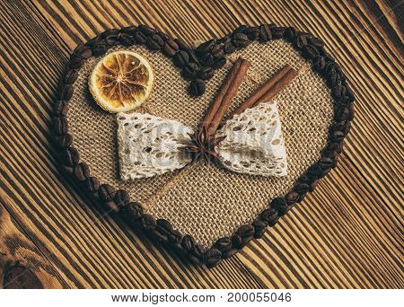 heart, coffee and love concept - heart decorated with burlap coffee lemon and cinnamon on wooden background