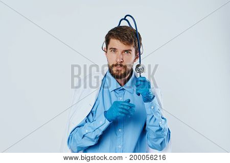 Man with a beard on a light background in medical clothes, a stethoscope.