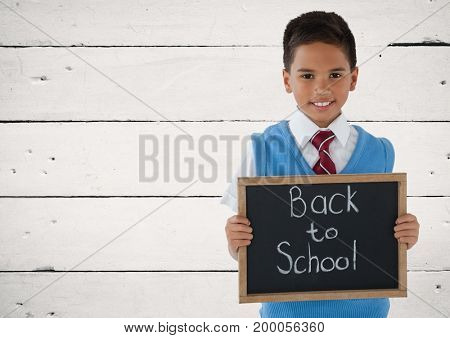 Digital composite of Schoolboy holding blackboard with Back to school text