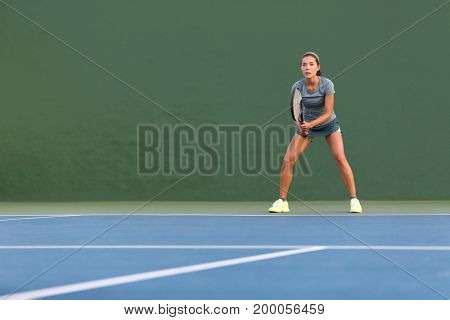 Tennis player woman standing ready to play waiting to receive serve. Outdoor fitness instructor focused playing on hard court on green background.