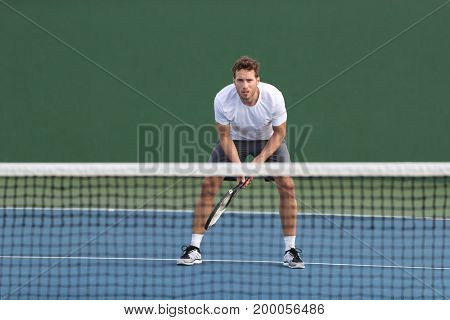 Professional tennis player man athlete waiting to receive ball, playing game on hard court. Fitness person focused behind net ready to return training cardio on outdoor sport activity.