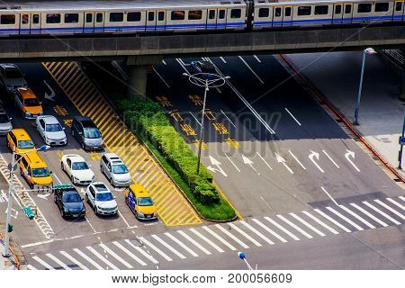 TAIPEI TAIWAN - JUNE 21: This is an aerial view of a Taipei mrt train arriving in the station and a ctiy road with cars waiting at a traffic light on June 21 2017 in Taipei