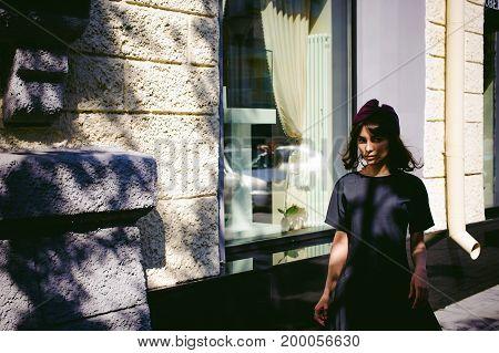Beautiful Woman In A Dark Stylish Dress Strolls Along The Street, Near Boutiques. Portrait Of A Fash