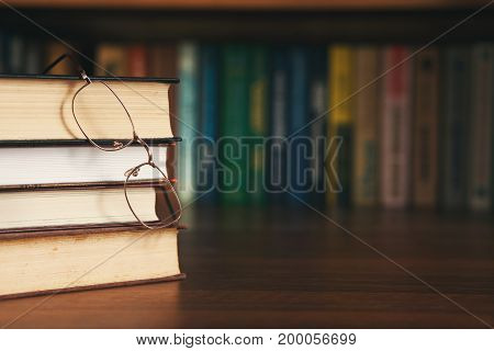education, science and books concept - pile of books and glasses
