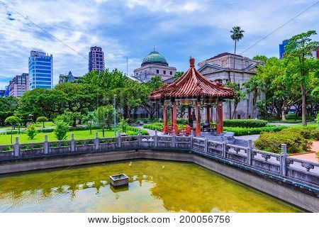 TAIPEI TAIWAN - JUNE 20: This is a view of the 228 memorial peace park with the National Taiwan museum architecture and city buildings in the background on June 20 2017 in Taipei