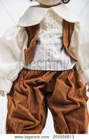 Portrait of ceramic porcelain handmade vintage doll of brunette boy with curly hair in in old brown crumpled velour masquerade costume with vest and elegant shirt with embroidery on white background.