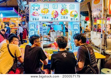 TAIPEI TAIWAN - JUNE 19: This is a group of Taiwanese people sitting at a shaved ice dessert vendor in the Raohe street night market on June 19 2017 in Taipei