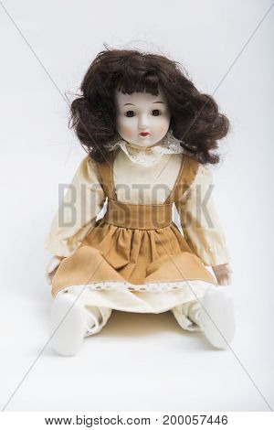 Portrait of sitting ceramic porcelain handmade vintage brunette doll with wavy hair in old beige textile sarafan dress with embroidery, in white shirt, shoes on white background.