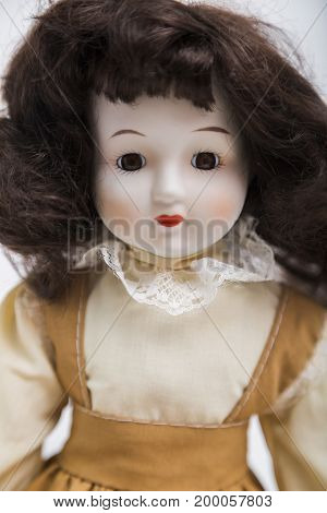Portrait of sitting ceramic porcelain handmade vintage brunette doll with wavy hair in old beige textile sarafan dress with embroidery, in white shirt on white background.