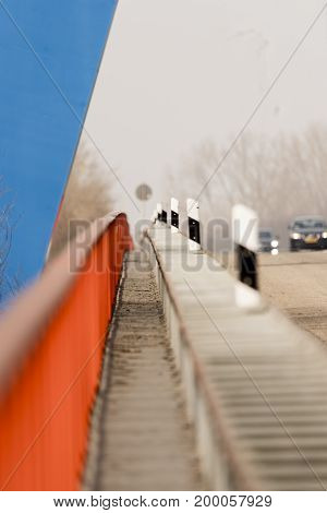 Small footpath over a highway bridge with red railings