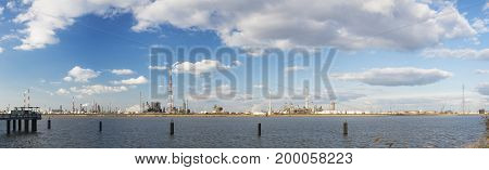 Panorama of a large industrial area with tall flare stacks in the port of Antwerp Belgium with lots of distillation towers and a jetty in the foreground.