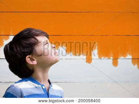 Digital composite of Boy looking upwards next to painted orange wall