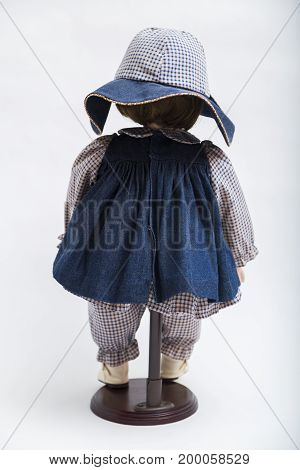 Portrait of ceramic porcelain handmade vintage brunette no face doll standing with her back in old blue denim dress, big hat, bow, plaid shirt, pants and boots on white background.