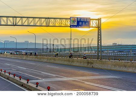 Highway on a bridge with Welcome to New Taipei city sign during sunset