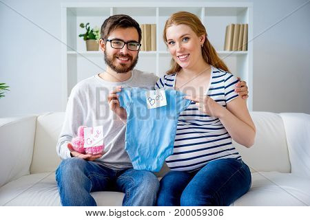 Couple choosing clothes for their unborn baby