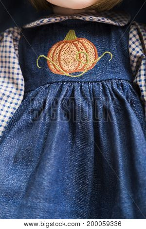 Ceramic porcelain handmade vintage no face doll in old blue denim dress with orange pumpkin embroidery, plaid shirt on white background.