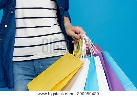 Woman on blue background holds packages, shopping.