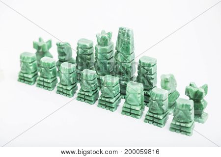 Shiny green stone vintage old handmade chess pieces on white background.