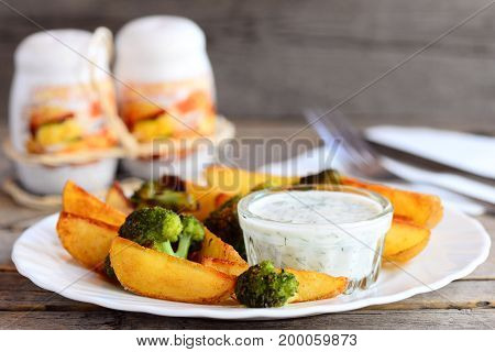 Roasted potatoes and broccoli with sauce on a plate and a wooden table. Home roasted potatoes and broccoli recipe idea. Fork, knife, salt and pepper shaker on an old wooden background
