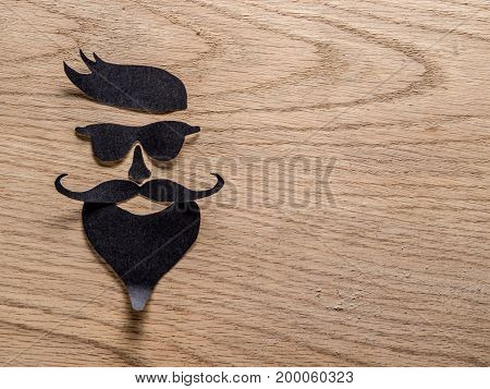 Hipster's definicial facial look cut from paper on the wooden background.