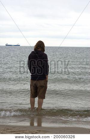 Man in a hooded sweatshirt wading in baltic sea