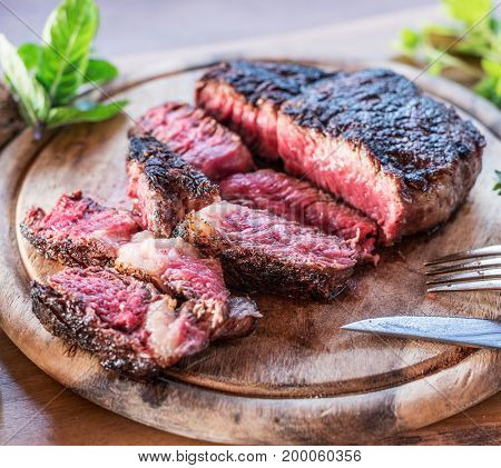 Medium rare Ribeye steak or beef steak on the wooden tray with herbs.