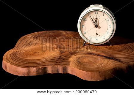 Old alarm clock five to twelve on a wooden board