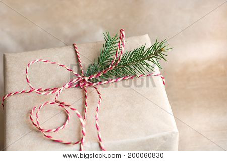 Christmas or new year gift box with red ribbon from craft paper. Close up.
