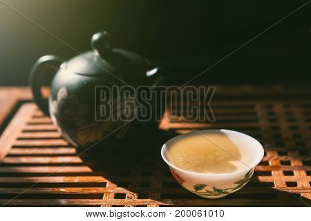 Chinese tea ceremony. Teapot and a cup of green puer tea on wooden table. Asian traditional culture