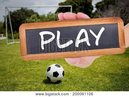 Digital composite of play text on blackboard with soccer field and football