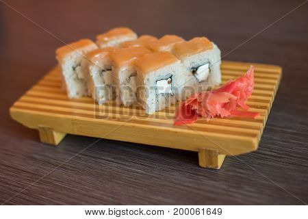Japanese food on a wooden plate of sushi rolls with fish and rice red ginger and green wasabi