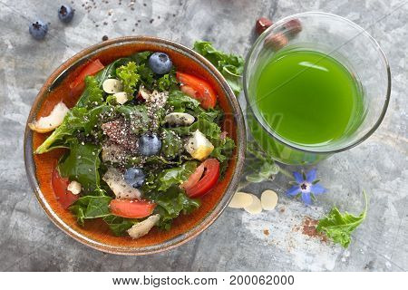 Kale salad with blueberry, tomato, nut and chia seeds and green kale smoothie.