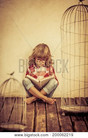 Happy child reading the book at home