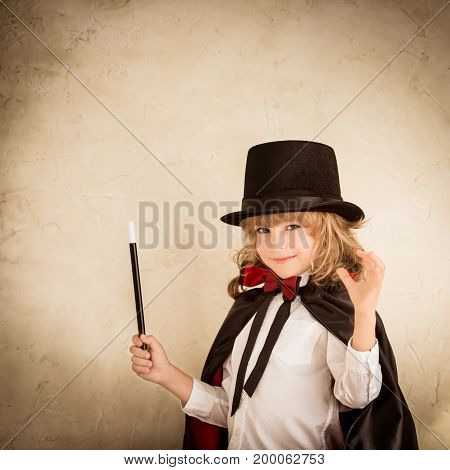 Child magician holding wand. Success and imagination concept
