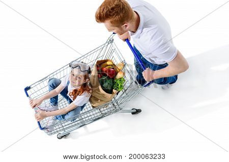 overhead view of father looking at cute little daughter sitting in shopping trolley isolated on white