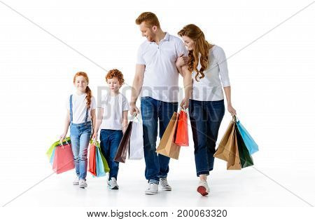 happy young family with paper bags walking together isolated on white
