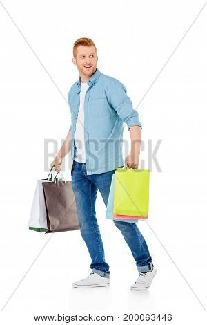 smiling young man holding colorful paper bags and looking away isolated on white