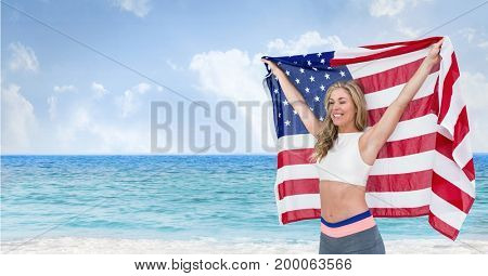 Digital composite of Happy woman holding a USA flag in the beach