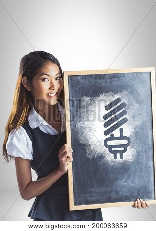 Digital composite of Girl holding blackboard with light bulb energy