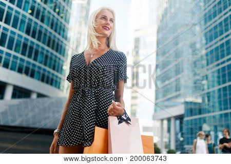 Photo of woman with shopping outside on buildings during day