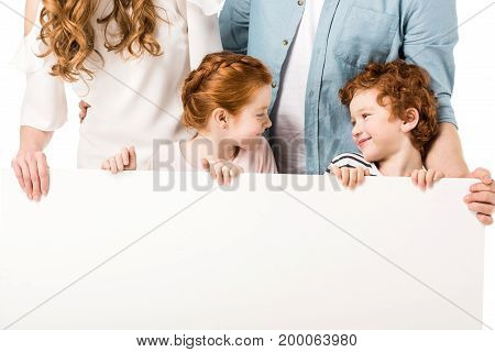 cropped shot of young family with two kids holding blank banner isolated on white